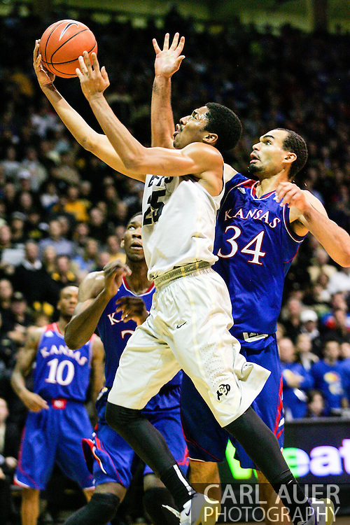 December 7th, 2013:  Colorado Buffaloes junior guard Spencer Dinwiddie (25) glides to the basket past Kansas Jayhawks sophomore forward Perry Ellis (34) in the second half of the NCAA Basketball game between the Kansas Jayhawks and the University of Colorado Buffaloes at the Coors Events Center in Boulder, Colorado