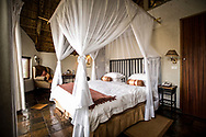 A canopy bed with mosquito netting in a private bungalow at Tau Game Lodge, a five-star lodge specializing in Big 5 game safaris and bird watching, South Africa.