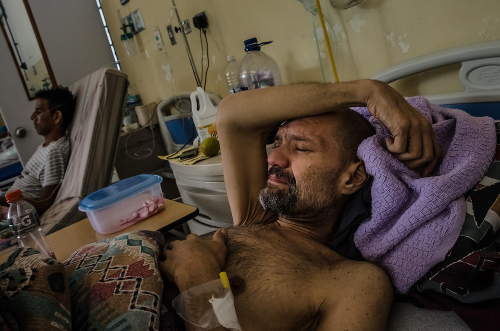 CARACAS, VENEZUELA - JANUARY 22, 2015: AIDS patient, Franco Bigotti, 47, cries as he describes the pain he is feeling to a visitor at a state-run hospital outside of Caracas. A few months ago, Mr. Bigotti and fellow AIDS patients at this hospital went nearly three months without their antiretroviral medicines, that the government provides them free-of charge when they're available.  Doctors at the hospital said that because of the shortages, they are working with a bare minimum of supplies, and that patients often die because of a lack of resources. Despite being a petro-state with one of the largest oil reserves in the world, basic and advanced medical supplies from gauze and surgical gloves, to heart stints, are difficult to find in hospitals and pharmacies across Venezuela.