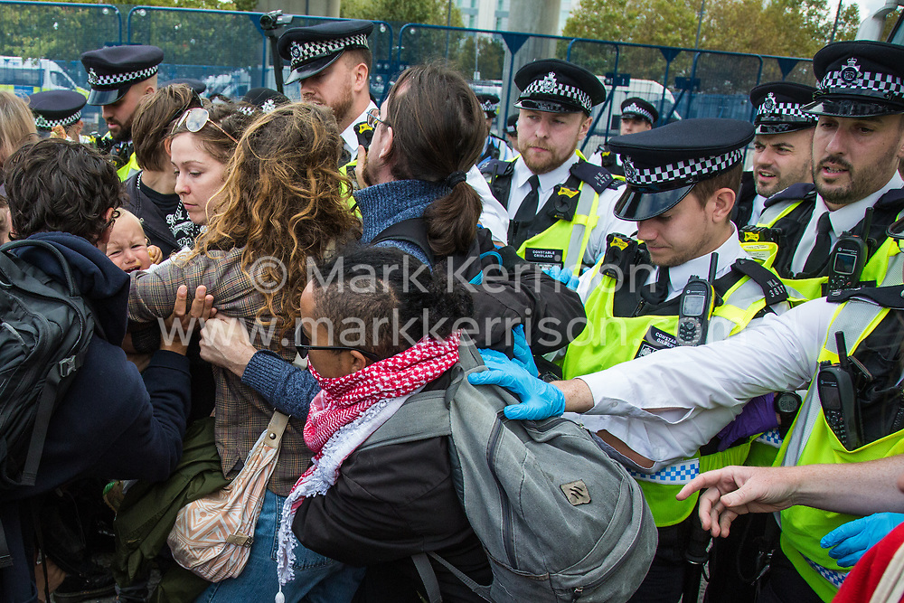 London, UK. 7 September, 2019. A very young child holding onto his mother is distressed as Metropolitan Police officers attempt to force back activists blocking the road in front of a truck attempting to deliver to ExCel London during the sixth day of Stop The Arms Fair protests against DSEI, the world's largest arms fair. The sixth day of protests was billed as a Festival of Resistance and included performances, entertainment for children and workshops as well as activities intended to disrupt deliveries to ExCel London for the arms fair.
