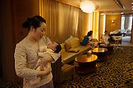 Shanghai, 21 septembre 2012.Dans un salon de la clinique  VIP Care Bay specialisee dans les soins post-natals, Lu Yan tient dans ses bras le nouveau-ne Hehe. Lu Yan est infirmière dediee a Hehe et a sa maman. Pendant le mois que durera leur séjour a la clinique, elle sera a leurs cotes, 24 heures sur 24, 7 jours sur 7..