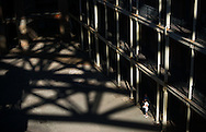 Visitors  to Fort Point, San Francisco, look up at the structure of the Golden Gate Bridge above, as it casts a pattern of light and shadow on the courtyard of the fort