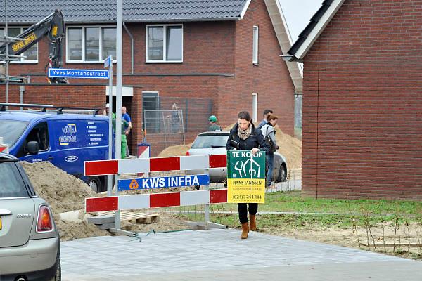 Nederland, Nijmegen, 1-5-2012Bouwvakkers zijn bezig met het bouwen van huizen in de nieuwe wijk Laauwik, onderdeel van de stadsuitbreiding de Waalsprong van Nijmegen in Lent. Een medewerkster van een makelaarskantoor loopt met het te koop bord weg van een huis wat verkocht is en waar de makelaar met de nieuwe bewoners naar binnen zal gaan, rechts op de achtergrond. Door de slechte economische situatie worden veel van de nieuwbouwplannen gewijzigd of uitgesteld.Foto: Flip Franssen/Hollandse Hoogte
