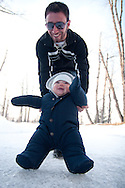 A father pushes his smiling and happy baby son across a frozen river sliding as he goes.