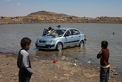 Syria.<br /> Young boys cleaning their car by hand in a small pond while woman washing by hand wool few meters away, Syria,<br /> 15th June 2013<br /> Picture by Daniel Leal-Olivas / i-Images