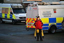 © Licensed to London News Pictures. 13/01/2017. Jaywick, UK.  A member of a search and rescue team stands next to an Incident Command Vehicle on the seafront at Jaywick before Homes are evacuated in Jaywick, Essex  due to the threat of flooding in low-lying areas . Photo credit: Ben Cawthra/LNP