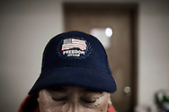 "OHIO, Toledo, October 27, 2012:  A volunteer standing with the blue baseball hat with the word ""freedom"" inside the ""Primera Iglesia Bautista"" where clothes and food is being distributed. ALESSIO ROMENZI"