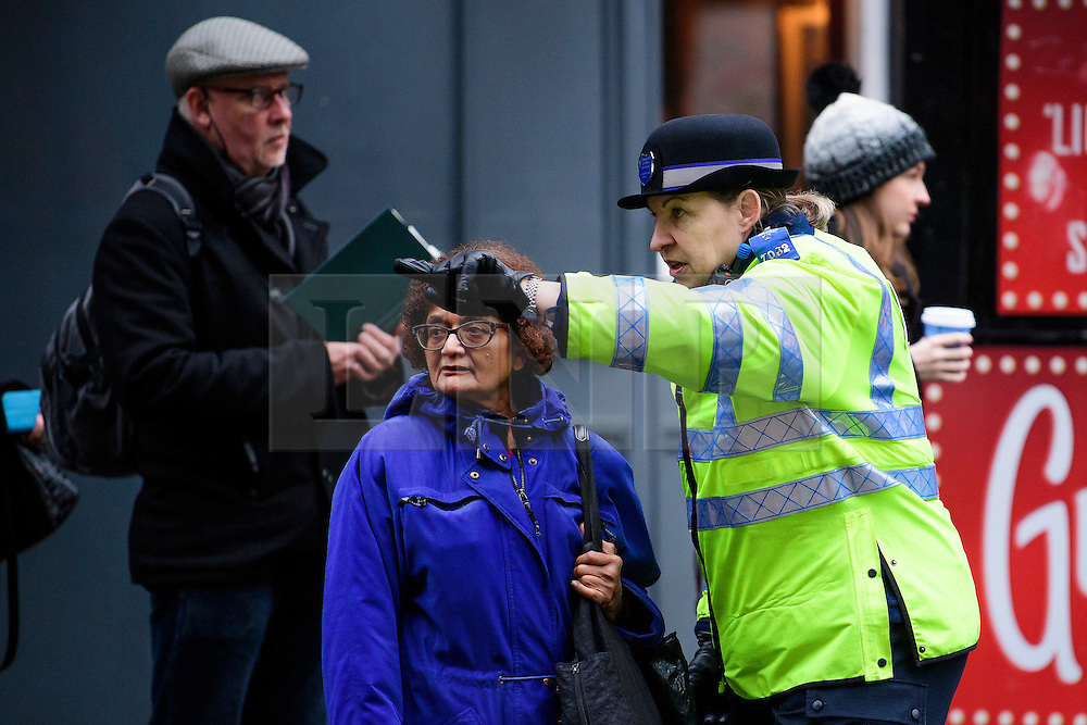 © Licensed to London News Pictures. 09/01/2017. London, UK.  A police officer helps a commuter as long queues of people wait for buses at Victoria station in London on the second day of a 24 hour tube strike.  All Zone one tube stations are closed until 6PM tonight after members of the RMT and the Transport Salaried Staffs' Association unions walked out after talks with TFL collapsed. Photo credit: Ben Cawthra/LNP