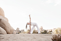 Mature woman in yoga triangle pose while enjoying a beautiful desert landscape.