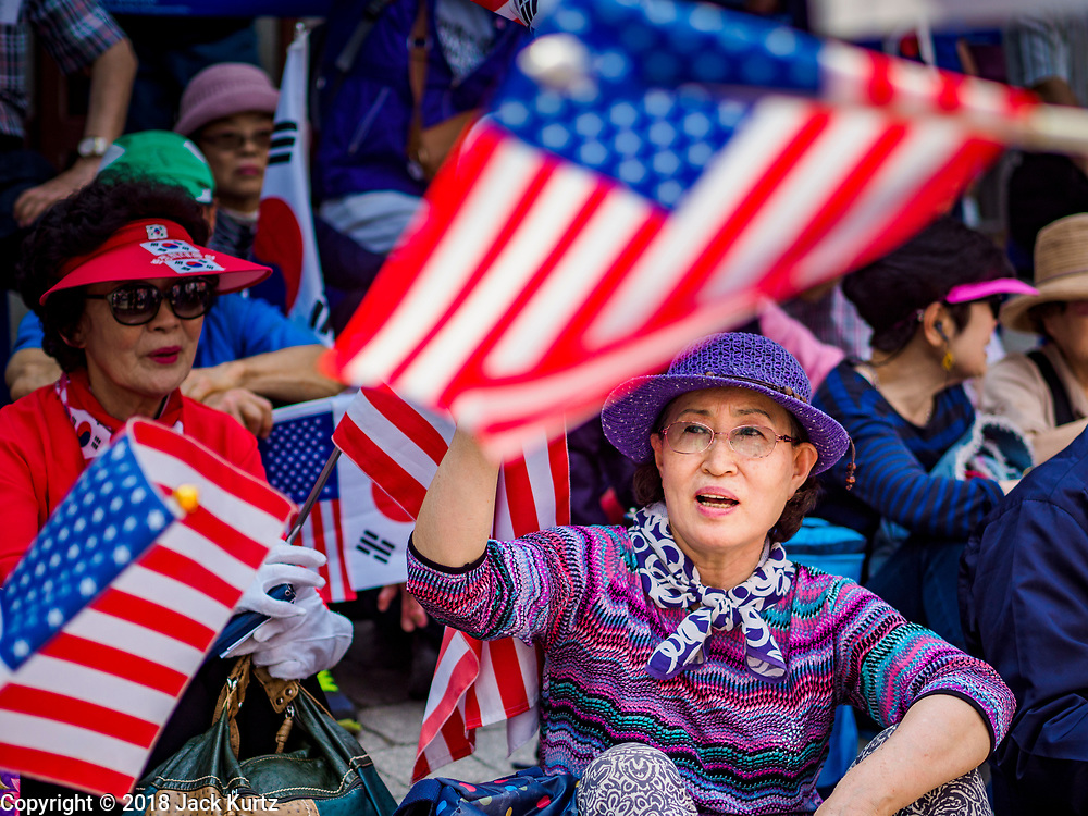 16 JUNE 2018 - SEOUL, SOUTH KOREA: South Koreans waving South Korean and American flags during a protest against South Korean President Moon Jae-in. Most of the protesters support jailed former President Park Geun-hye. President Moon Jae-in was elected in 2017 after Park was impeached, tried and convicted on corruption charges. The protesters allege that Moon is too soft on North Korea and can't be trusted to negotiate with North Korean leader Kim Jong-un. They support US President Donald Trump's efforts to negotiate with the North Korean strongman.   PHOTO BY JACK KURTZ