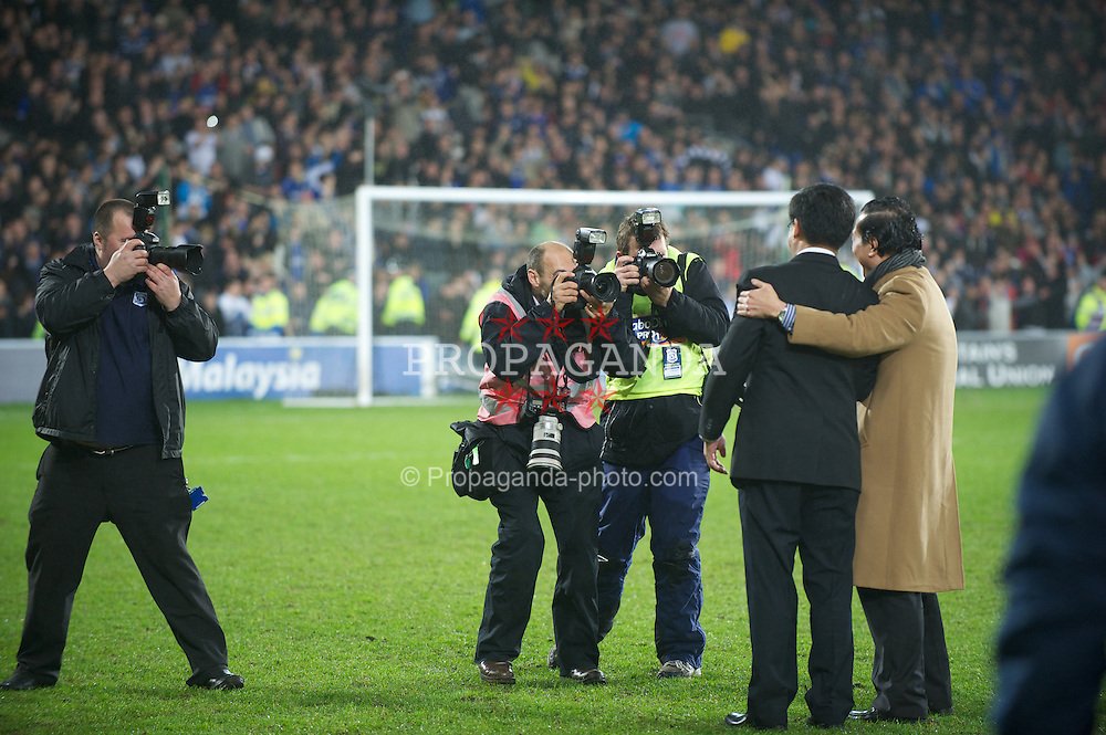 CARDIFF, WALES - Tuesday, January 24, 2012: Photographer's on the pitch take photographs of Cardiff City's owners Tan Sri Vincent Tan Chee Yioun and Datuk Chan Tien Ghee after the penalty shoot-out victory over Crystal Palace during the Football League Cup Semi-Final 2nd Leg at the Cardiff City Stadium. (Pic by David Rawcliffe/Propaganda)