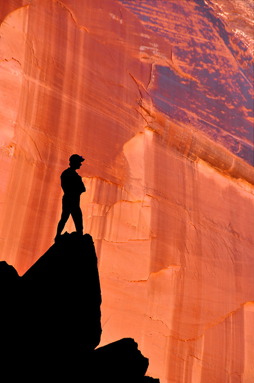 Hiker silhouetted against canyon wall in Arizona's Paria Canyon - Vermilion Cliffs Wilderness.