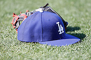 LOS ANGELES, CA - AUGUST 07:  A Los Angeles Dodgers cap and glove lie on the grass during batting practice before the game against the Colorado Rockies on Tuesday, August 7, 2012 at Dodger Stadium in Los Angeles, California. The Rockies won the game 3-1. (Photo by Paul Spinelli/MLB Photos via Getty Images)