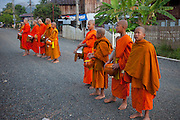 In Ban Phan Luang, across the Nam Khan River from Luang Prabang, Laos. Every morning at dawn, Buddhist monks walk down the streets collecting food alms from devout, kneeling Buddhists. In neighborhoods, after receiving food, they line up and chant a blessing towards the benefactor's house.They then return to their temples, or wats, and eat together. This procession is called Tak Bat, or Making Merit.