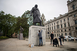 "© Licensed to London News Pictures. 08/06/2020. London, UK. Members of the public, who started at 2:30am, attempt to remove Graffiti from a statue of former British Prime Minister Winston Churchill in Parliament Square, after it was graffitied with the words ""was a racist"" during a Black Lives Matter demonstration In central London. The death of George Floyd, who died after being restrained by a police officer In Minneapolis, Minnesota, caused widespread rioting and looting across the USA. Photo credit: Ben Cawthra/LNP"