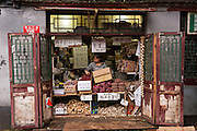 A woman works in her traditional shop selling root vegatables along a hutong in Beijing, China