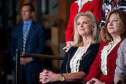 "ANN ROMNEY looks on as her husband speaks at a warehouse in Chantilly, Va. Republican Presidential Candidate Mitt Romney campaigned Wednesday in Northern Virginia, a region of a key swing state that is critical for Romney. Obama won Virginia in 2008. Romney spoke to an audience filled with women business owners saying he's running to ""help your enterprises."""