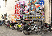 Cycles by colourful event posters on noticeboard, Maastricht, Limburg province, Netherlands,