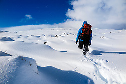 Back View of Mountaineer Climbing Snowy Mountain