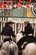 Two women on horseback conversing at the April Fair, Seville, Spain.