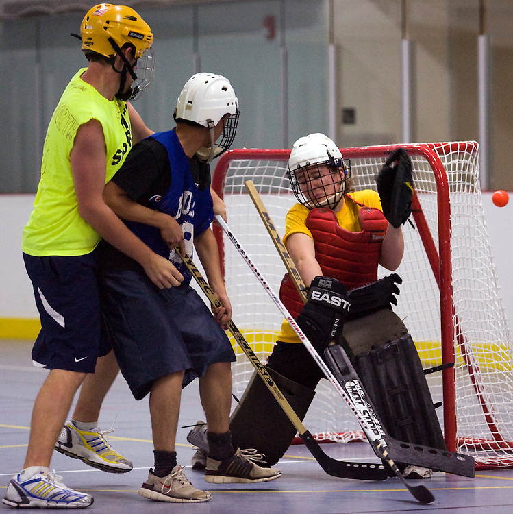 -November 4, 2009, Boston, MA-..Vagiants goaltender Lizzy Snell, right, makes a save as Giants player Zach Farnsworth, left, defends.  The Vagiants faced the Little Brown Filipino Warriors in the first round of the Co-Ed Floor Hockey Championships at the Boston University Fitness and Recreation Center on Wednesday night.  The Vagiants won, 3-1, assuring a spot in the Championships on Sunday, when they hope to repeat their 2008 success...(Photo by Brooks Canaday)