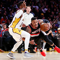 26 March 2016: Portland Trail Blazers guard Damian Lillard (0) drives past Los Angeles Lakers guard David Nwaba (10) during the Portland Trail Blazers 97-81 victory over the Los Angeles Lakers, at the Staples Center, Los Angeles, California, USA.