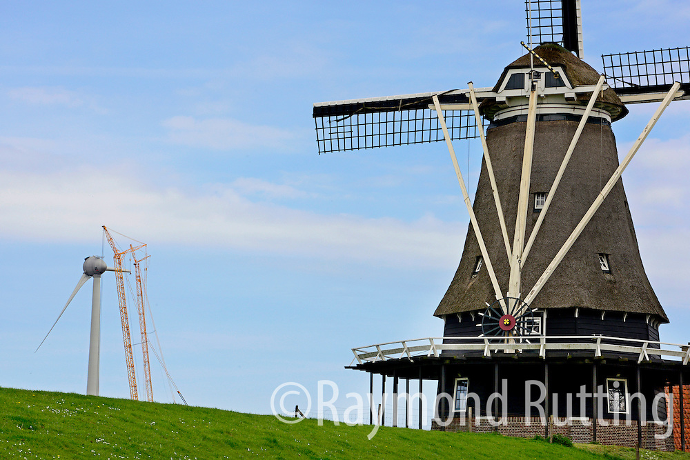 """Netherlands - Medemblik - Old and New. On the background, de Ambtenaar, the highest windmill of Europe is in Medemblik (Netherlands) is located in the Wieringermeer near Medemblik?  Windmill """"The Ambtenaar """" in the Wieringermeer. Windmills convert wind into energy. Ambtenaar Wind Farm is renewed. An old wind turbine of 1 MW has been replaced with a 7.5 MW Enercon E126. This new wind turbine provides 13,000 residents of Wieringermeer with green electricity and ensures 12,000 tonnes less of CO2 emissions annually. photo raymond rutting"""