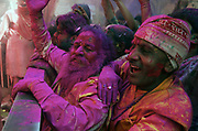 """Revellers gather at the Shriji Temple (Laadli Sarkar Mahal), during Lathmar Holi, smeared with coloured powder. It is held during a full moon and the town becomes swamped with tourists and revellers making the pilgrimage for a glimpse of """"God"""", the Lord Shiva, who is revealed inside the temple only fleetingly."""