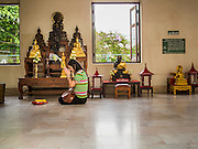 12 MARCH 2015 - BANGKOK, THAILAND:  A woman prays in a chapel at the City Pillar Shrine in Bangkok. Bangkok's city pillar shrine (also known as San Lak Muang) is one of the most important city pillar shrines in Thailand. The shrine is in the heart of Bangkok, opposite the grand palace in the southeast corner of the Sanam Luang and close to the Ministry of Defence. The shrine was built after the establishment of the Rattanakosin Kingdom (Bangkok) to replace the old capital of the Thonburi Kingdom during the reign of King Rama I in 1782. It was intended to be the spiritual center for Thai citizens.     PHOTO BY JACK KURTZ