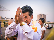"""31 JANUARY 2013 - PHNOM PENH, CAMBODIA:  A man prays for former King Norodom Sihanouk in front of the Royal Palace in Phnom Penh. Sihanouk (31 October 1922- 15 October 2012) was the King of Cambodia from 1941 to 1955 and again from 1993 to 2004. He was the effective ruler of Cambodia from 1953 to 1970. After his second abdication in 2004, he was given the honorific of """"The King-Father of Cambodia."""" Sihanouk served two terms as king, two as sovereign prince, one as president, two as prime minister, as well as numerous positions as leader of various governments-in-exile. He served as puppet head of state for the Khmer Rouge government in 1975-1976. Most of these positions were only honorific, including the last position as constitutional king of Cambodia. Sihanouk's actual period of effective rule over Cambodia was from 9 November 1953, when Cambodia gained its independence from France, until 18 March 1970, when General Lon Nol and the National Assembly deposed him. Upon his final abdication, the Cambodian throne council appointed Norodom Sihamoni, one of Sihanouk's sons, as the new king. Sihanouk died in Beijing, China, where he was receiving medical care, on Oct. 15, 2012. His funeral procession, which will wind through Phnom Penh is Friday, Feb.1 and his cremation is on Feb. 4, 2013. Over a million people are expected to attend the service.    PHOTO BY JACK KURTZ"""