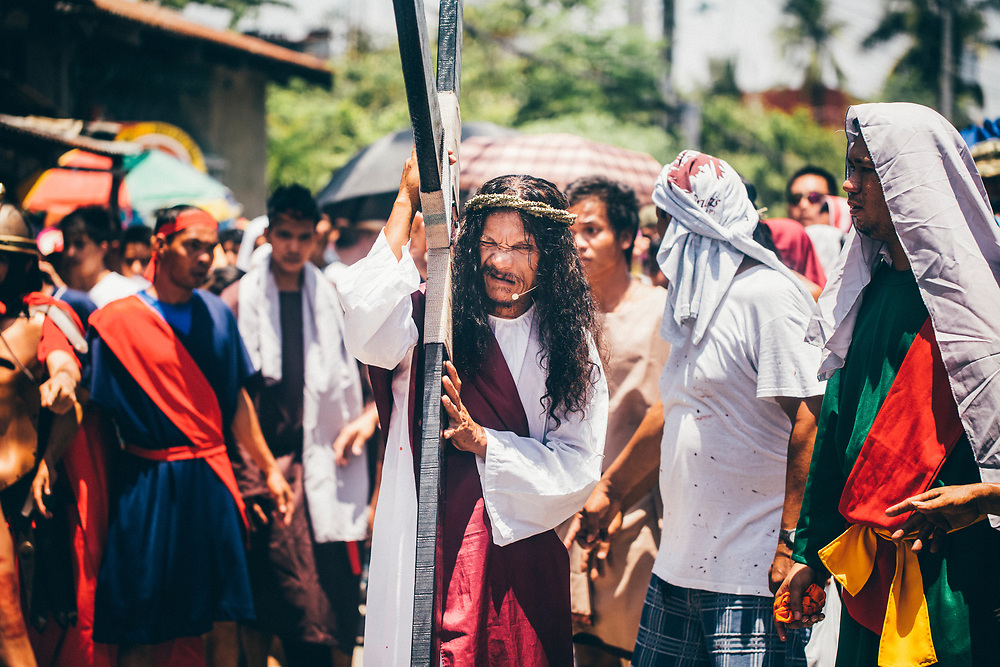 Ruben Enaje, playing the role of Jesus Christ, is led through the streets of Cutud, the Philippines, during the Holy Week festival.