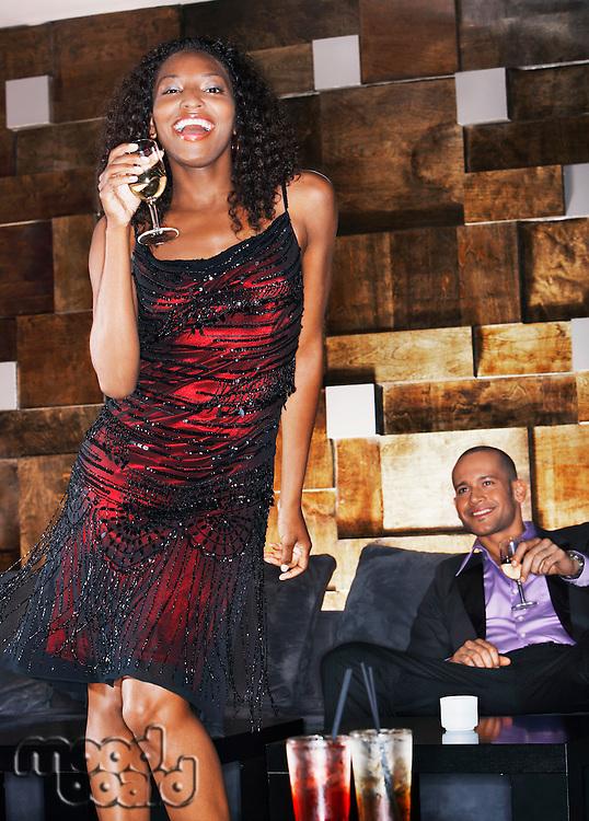 Woman holding drink dancing in bar portrait