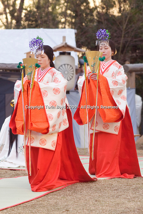 """Dec. 17, 2009: These are miko shrine maidens performing a special Shinto Shaden Kagura dance ritual during the annual On-Matsuri festival, a traditional Shinto religious festival held at the Kasuga Wakamiya Shrine in the ancient Japanese city of Nara, Japan. In older days, miko were considered shamans, but today they take on a more lighter role as priestesses or ceremonial duties. The traditional miko costume is an elaborate multi layered costumed kimono comprised of a red hakama (long, kimono type trousers), a white haori or kimono outer layer, white or red hair ribbons (white symbolizes purity), and in the case of Kasuga Shrine miko, they wear wisteria flowers in their headdress,  symbolic if the shrine's patron the Fujiwara clan. ..This festival which dates back to the twelfth century was first started by Tadamichi Fujiwara, Chief Advisor of the Emperor in 1136 as a way to pray for the eradication of a plague as well as hopes of a bumper crop in the coming year. For many centuries this festival included both Shinto and Buddhist participants, but when Shinto was made the official state religion during the Meiji period (1867-192), the government instituted a policy of separation between Buddhism and Shinto. Ever since, this festival has strictly been a Shinto ceremony held every December 17 on the grounds of Kasuga Taisha Grand Shrine, which Kasuga Wakamiya Shrine is a branch of. During the festival, the Divine Spirit of Wakamiya is temporarily enshrined in the Otabisho, a special shrine set up for just this festival. Several official religious rites are performed throughout the day, as well as the Jidai Gyrotesu, or """"Precession of Eras"""" in which parade participants displays traditional Japanese costumes from various era of Japanese history. There are also displays of court music and dance which goes on well into the night."""