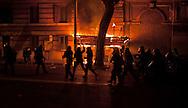 Roma  15 Ottobre 2011.Manifestazione contro la crisi e l'austerità.Scontri tra manifestanti e forze dell'ordine.Le forze dell'ordine avanzano in via Merulana sullo sfondo una impalcatura  data alle fiamme dai manifestanti.