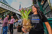 A group with We Are Family' t-shirts bring flowers for the staff of Black and Blue who sheltered them during the attack - Stoney street is soon thronging with lunchtime eaters and drinkers. The market reopening is signified by the ringing of the bell and is attended by Mayor Sadiq Khan. Tourists and locals soon flood back to bring the area back to life. London  14 June 2017.