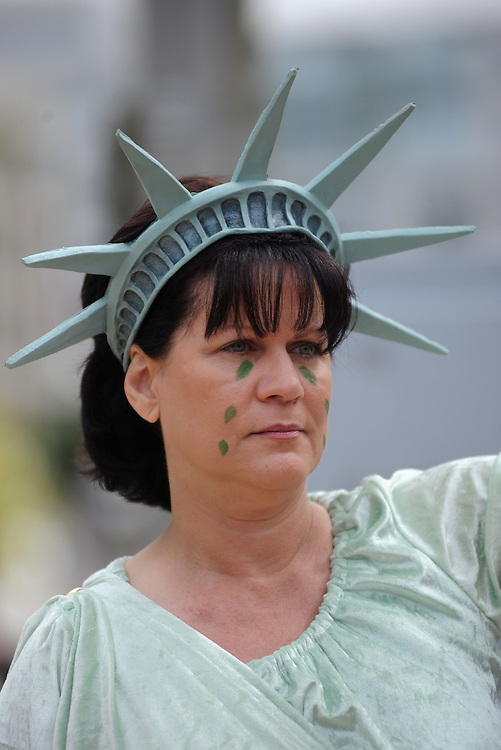 Sally Finch, of Missouri, dressed as Lady Liberty in tears, watches the crowd marche down Pennsylvania Ave. to the U.S. Capitol to have thier voices heard during the Tea Party Protest on Sept. 12, 2009 in Washington, DC.