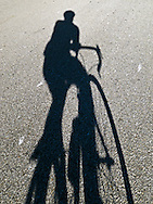 the shadow of a bicycle and rider on a paved road. WATERMARKS WILL NOT APPEAR ON PRINTS OR LICENSED IMAGES.