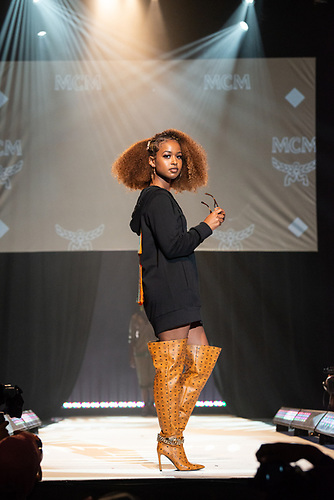 A model in a hooded dress and high-heeled orange boots poses on the runway at the Howard University Annual Fashion Show.