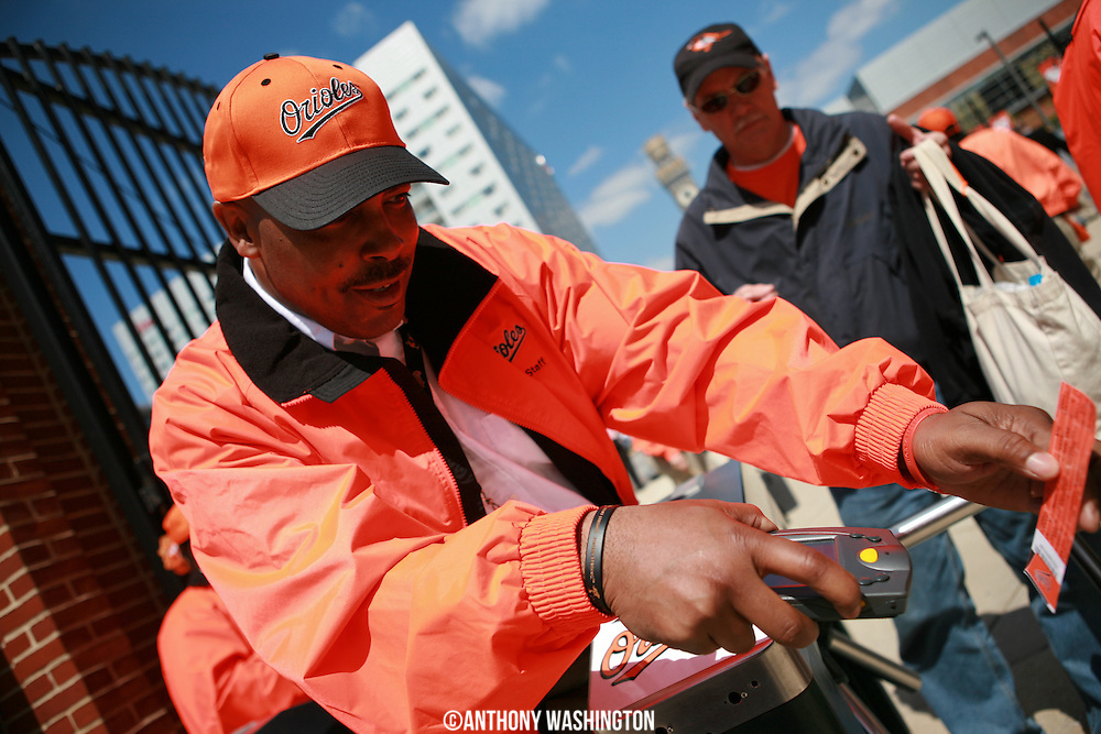 A ticket taker scans a ticket before the start of opening day at Oriole Park at Camden Yards on Friday, April 9, 2010.