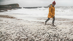 © Licensed to London News Pictures. 03/03/2019. West Bay, UK. A visitor to West Bay in Dorset walks on a foam flecked beach as storm Freya whips up the waves. Photo credit: Jason Bryant/LNP
