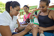 A health worker vaccinates a child during a vaccination session at the primary school in the town of Coyolito, Honduras on Wednesday April 24, 2013.