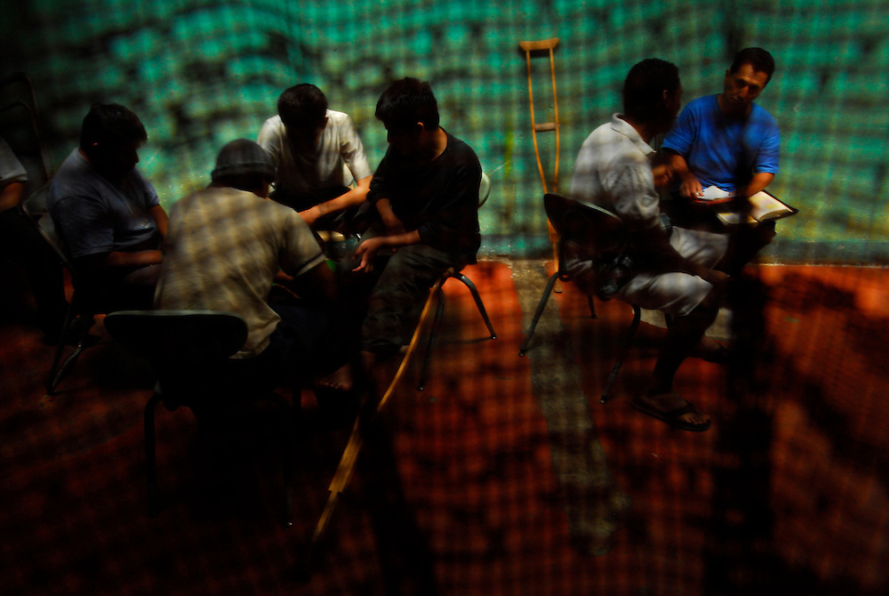 "Residents of Casa Hogar, a rehabilitation home for alcohol and drug addicts, outside of Antigua, Guatemala, play board games and study the Bible Sunday. Time weighs heavily on the residents and they try to fill every waking hour with something to keep themselves occupied. Religion plays an important role in the residents' recovery they say..Casa Hogar currently houses 44 men (with a maximum of 60.) Jorge Rosales, himself a former drug user, founded the home 2 years ago after he kicked his habit and left the garbage dump he had been living in for thirteen months...If accepted into Casa Hogar the voluntary residents must first spend 6 days in a first floor room of mattresses, are denied showers and must eat meals separately from other residents. Patients in the first floor zone suffer from convulsions, vomiting and other withdrawal symptoms and are monitored round the clock by a nurse. Most alcoholics who enter the program have been drinking rubbing alcohol, according to Rosales, because it is so inexpensive...""If they make it"" says resident Byron Rosales, ""they can join us up top."" It is up to the individual when they feel they are ready to leave the home."
