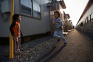 Children who's families lost everything in the tsunami March 11, 2011, are living at a temporary housing complex in Ishinomaki are playing in the evening sun.