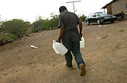 A man refills water jugs at a home along a trail paved by undocumented migrants who crossed illegally from Mexico into the United States onto the Tohono O'odham Nation in Arizona in the Sonoran Desert, USA.