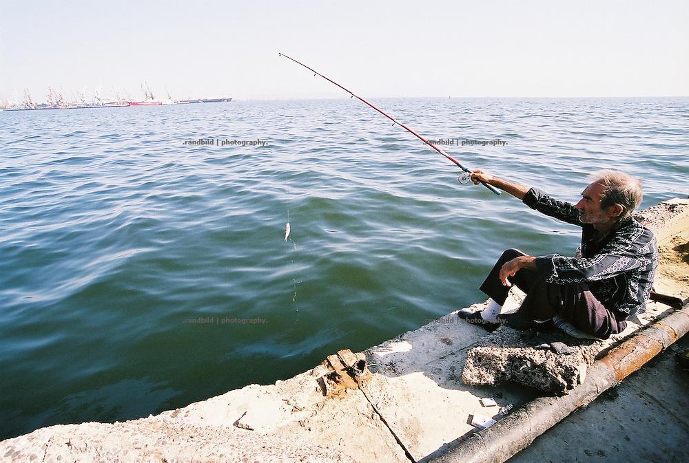 Im Hafen der aserbaidschanischen Hauptstadt Baku angeln auf einer Kaimauer alte Herren. Das Wasser ist von der Ölförderung im Kaspischen Meer verschmutz. Entsprechend keine Fische gehen ihnen an den Haken...A fisherman has catched a little fish in the port of Baku, Aserbaijan.