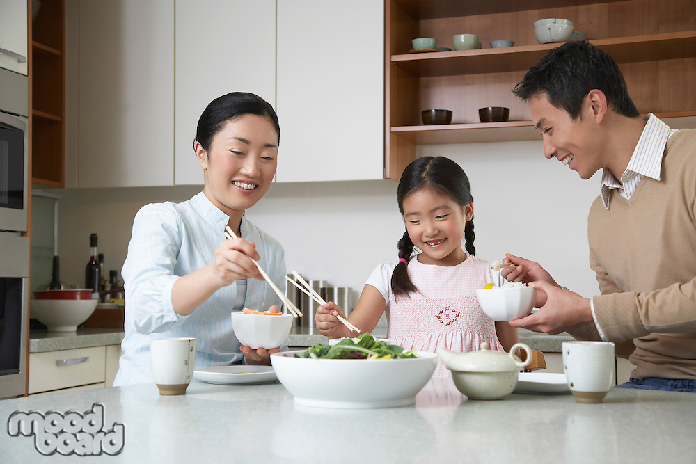 Young couple and daughter eating a meal with chopsticks on kitchen counter