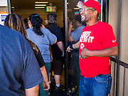 05 NOVEMBER 2013 - PHOENIX, AZ:    WILLIAM DAVENPORT, a worker at St. Mary's Food Bank in Phoenix, AZ, greets clients as the doors open. Demand at St. Mary's Food Bank has continued to increase even as government assistance is reduced. Over the summer, St. Mary's Phoenix location provided emergency food for 300 - 400 families per day. They are currently supporting about 600 families per day. Part of the increase is seasonal but a large part of it is no clients coming to the food bank for the first time. More than 1.1 million Arizonans who use the Supplemental Nutrition Assistance Program, known as food stamps, saw their benefits reduced Friday, Nov. 1, in a long-planned national cut that was tied to the economic stimulus which was a part of the American Recovery and Reinvestment Act. The cuts imposed last week range from $11 a month for a single recipient to $65 or more for large families. Many of SNAP receipients already use food banks to supplement their government assistance and the cuts in the SNAP program are expected to increase demand even more.   PHOTO BY JACK KURTZ