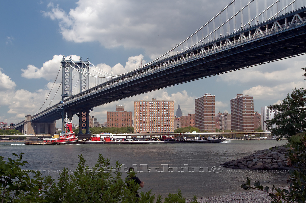 Tugboat and barge on East River under Manhattan Bridge.