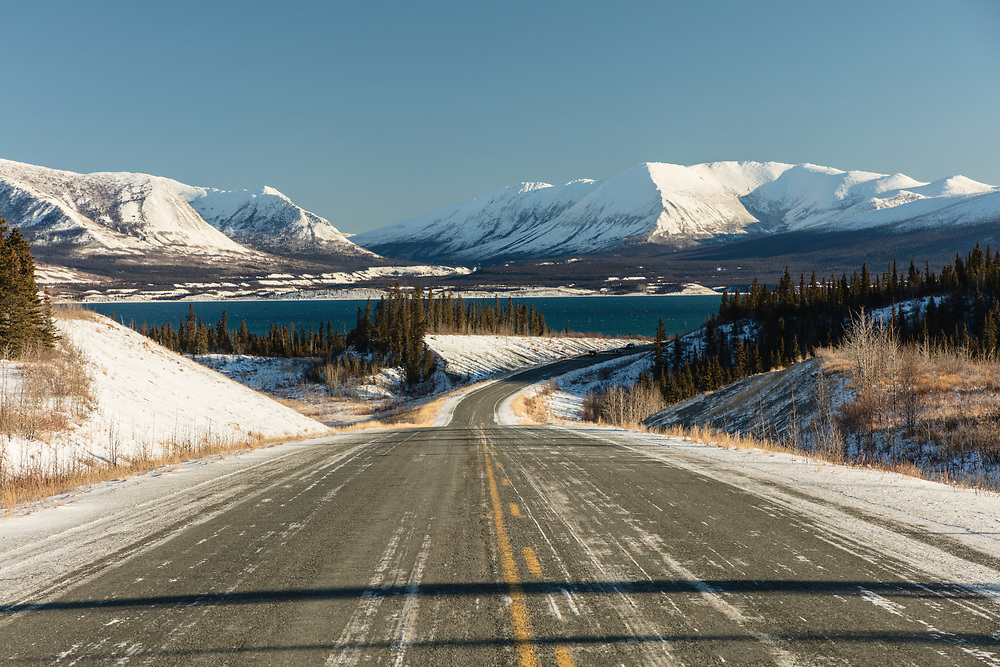 The Alaska Highway winds past Kluane Lake and Ruby Range mountains in the Yukon Territory. Winter. Afternoon.