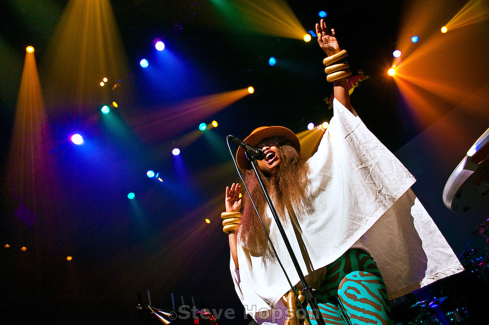 """Erykah Badu performing at ACL Live at the Moody Theater, Austin, Texas, October 11, 2012. Erica Abi Wright (born February 26, 1971), better known by her stage name Erykah Badu is a Grammy Award-winning American singer-songwriter, record producer, activist and actress. Her work includes elements from R&B, hip hop and jazz. She is known as the """"First Lady of Neo-Soul"""" or the """"Queen of Neo-Soul""""."""
